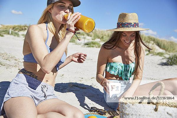 Junge Frau mit Freundin am Strand beim Trinken von Saft aus der Flasche