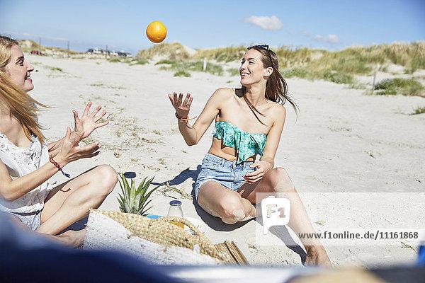 Zwei Freundinnen am Strand werfen eine Orange. Zwei Freundinnen am Strand werfen eine Orange.