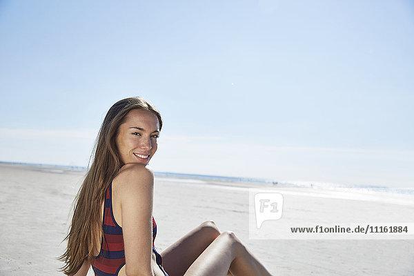 Lächelnde junge Frau am Strand sitzend