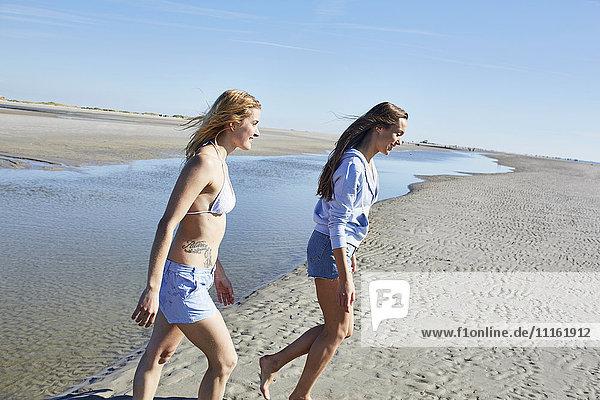 Zwei Freundinnen  die am Strand spazieren gehen.