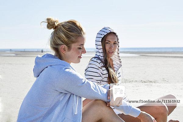 Zwei Freundinnen mit Kapuzenpullover am Strand