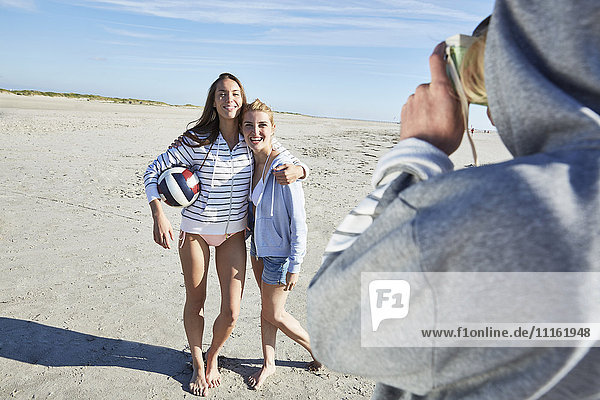 Mann beim Fotografieren von zwei Freunden mit Beachvolleyball am Strand