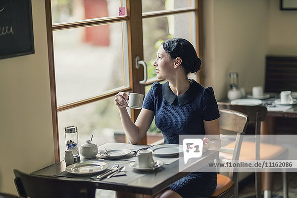 Junge Frau in einem Café mit Blick aus dem Fenster
