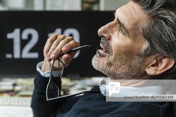 Erwachsener Mann mit Brille  der über Lösungen nachdenkt