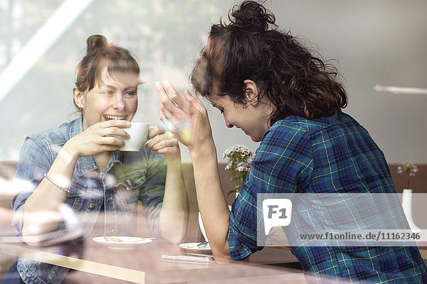 Zwei lachende Frauen sitzen hinter der Fensterscheibe eines Cafés.