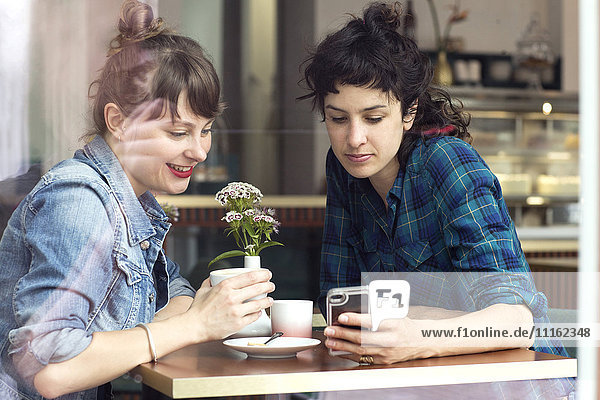 Two women sitting behind windowpane of a coffee shop looking at smartphone