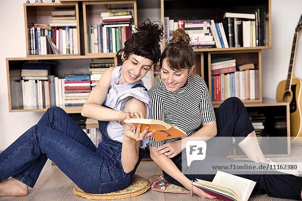 Zwei beste Freunde sitzen Rücken an Rücken auf dem Boden des Wohnzimmers und schauen sich ein Buch an.