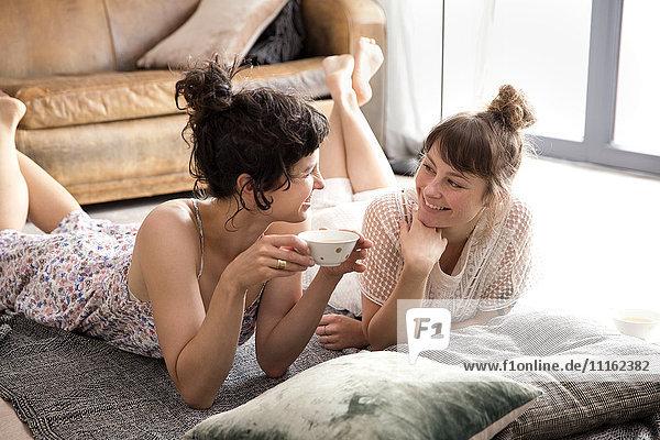 Zwei sprechende Freunde liegen auf einer Decke auf dem Boden des Wohnzimmers.