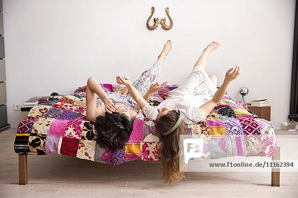 Zwei beste Freunde liegen auf dem Bett mit Beinen in der Luft und hören Musik mit Kopfhörern.