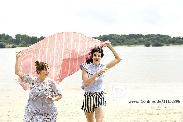 Zwei glückliche Freunde laufen Seite an Seite am Strand und halten das Tuch.