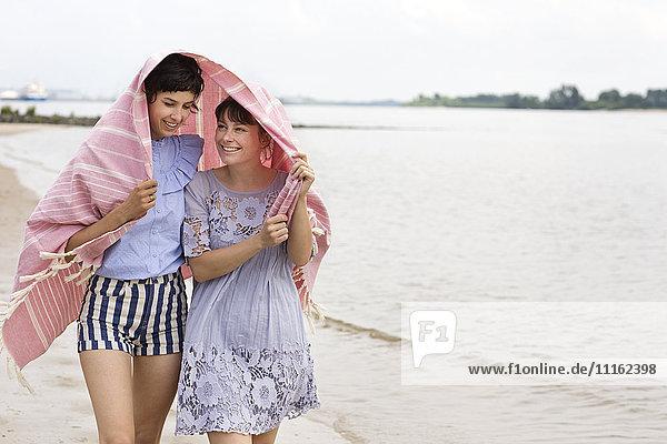 Zwei glückliche Freunde  die sich mit einem Tuch bedecken und Seite an Seite am Strand spazieren gehen.