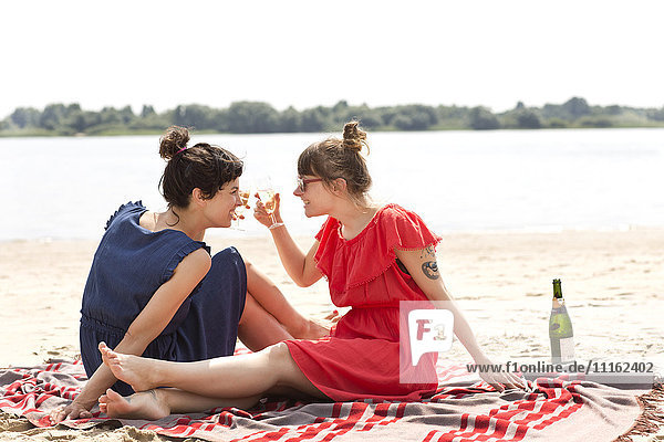 Zwei lächelnde Freunde sitzen am Strand und rösten mit einem Glas Sekt.
