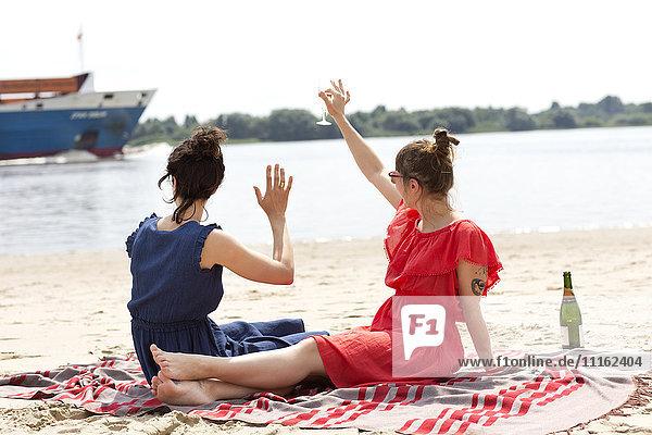 Zwei Freunde sitzen am Strand und stoßen mit einem Glas Sekt an.
