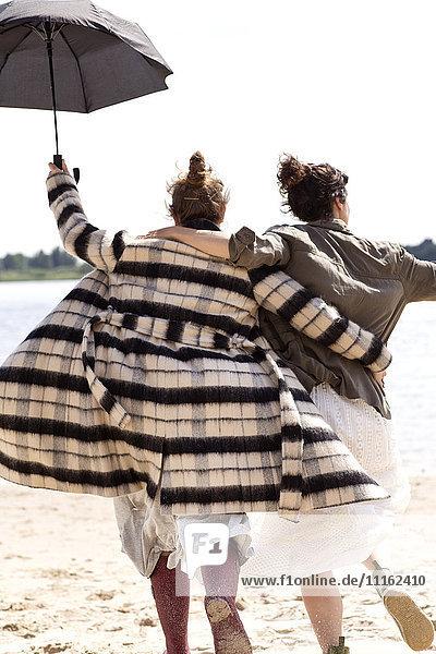 Rückansicht von zwei Freunden  die Seite an Seite am Strand mit einem Regenschirm laufen.