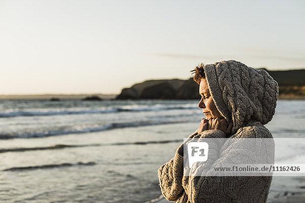 Frankreich  Halbinsel Crozon  Frau mit Strickjacke am Strand bei Sonnenuntergang