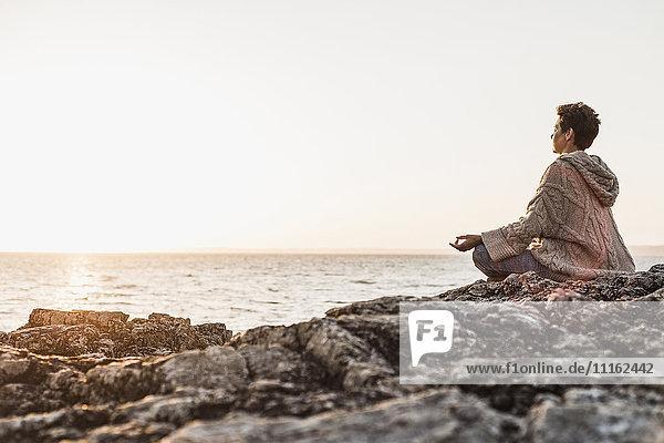 Frankreich  Halbinsel Crozon  Frau beim Meditieren am Strand bei Sonnenuntergang