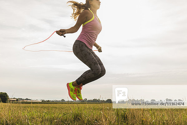 Junge Frau beim Seilhüpfen in ländlicher Landschaft