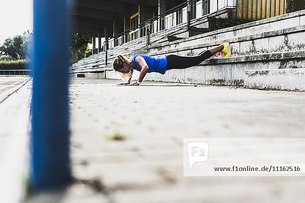 Young woman doing pushups on grandstand