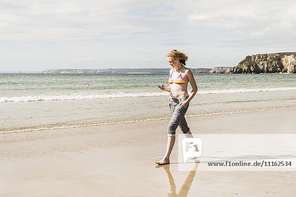 Teenagermädchen mit Handy am Strand unterwegs