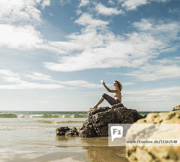 Teenager-Mädchen sitzt auf einem Felsen am Strand und nimmt einen Selfie.