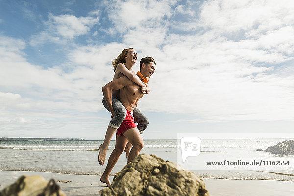 Fröhlicher junger Mann trägt Freundin Huckepack am Strand