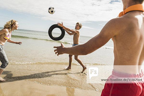Freunde beim Spielen mit Ball und Reifen am Strand