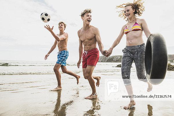 Freunde beim Laufen mit Ball und Reifen am Strand
