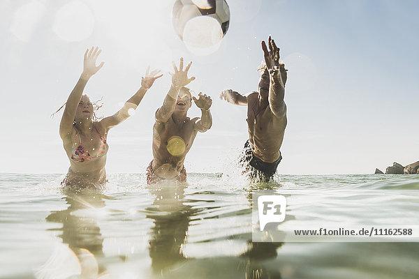 Freunde,  die mit einem Ball im Meer spielen.