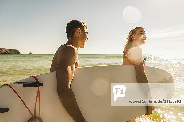 Teenager-Pärchen mit Surfbrett am Meer