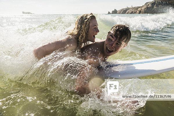 Teenager-Paar mit Spaß auf dem Surfbrett im Meer