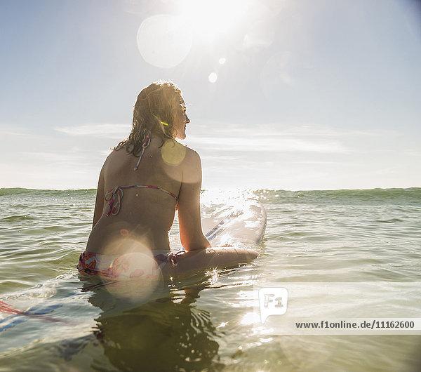 Teenager Mädchen mit Surfbrett im Meer
