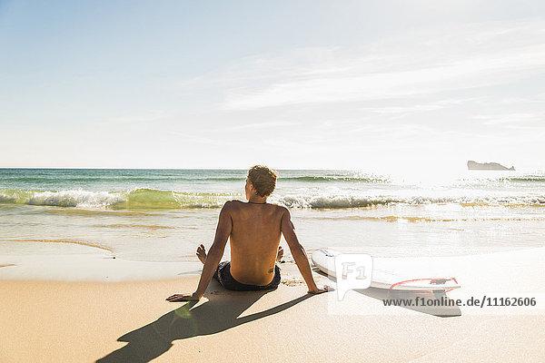 Teenager-Junge auf dem Surfbrett am Meer sitzend