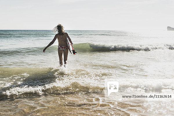 Teenager-Wandern mit Surfbrett ins Meer