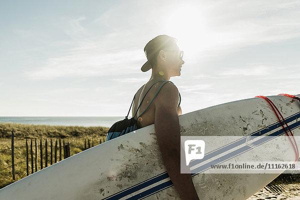Junger Mann mit Surfbrett an der Küste