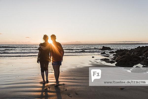 Frankreich  Halbinsel Corzon  Paar beim Sonnenuntergang am Strand spazieren gehen