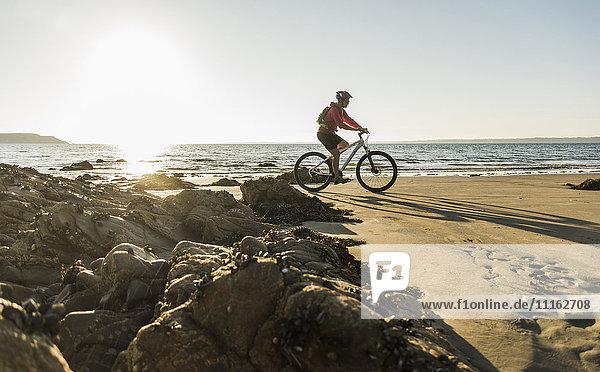 Frankreich  Halbinsel Crozon  Man Biking am Strand