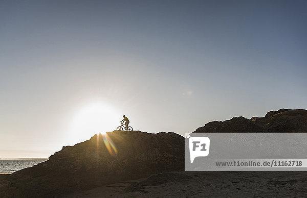 Frankreich  Halbinsel Crozon  Mountainbiker bei Sonnenuntergang