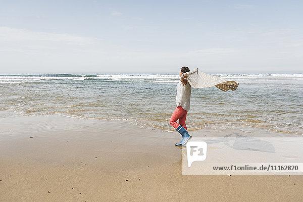 Reife Frau  die am Strand spazieren geht und eine Decke hebt.