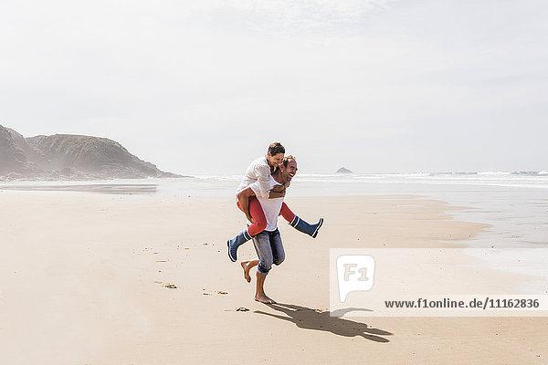 Glücklicher reifer Mann  der seine Frau huckepack am Strand trägt.