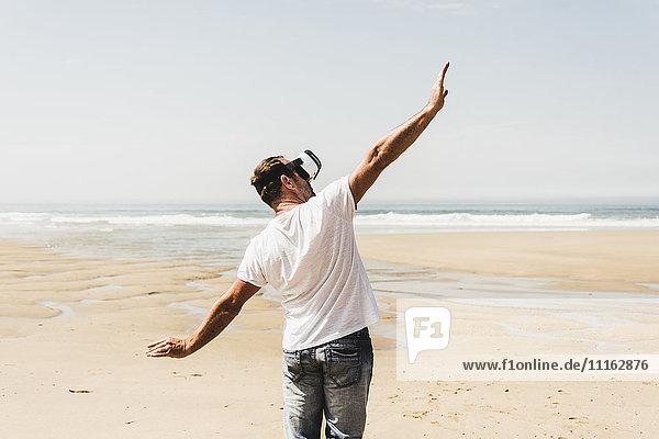 Erwachsener Mann am Strand stehend mit VR-Brille
