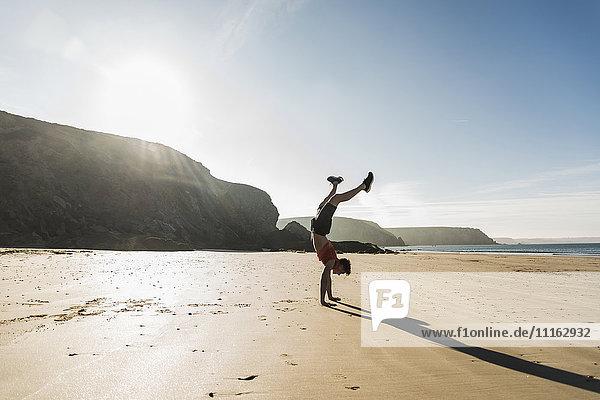 Frankreich  Halbinsel Crozon  junger Mann beim Handstand am Strand