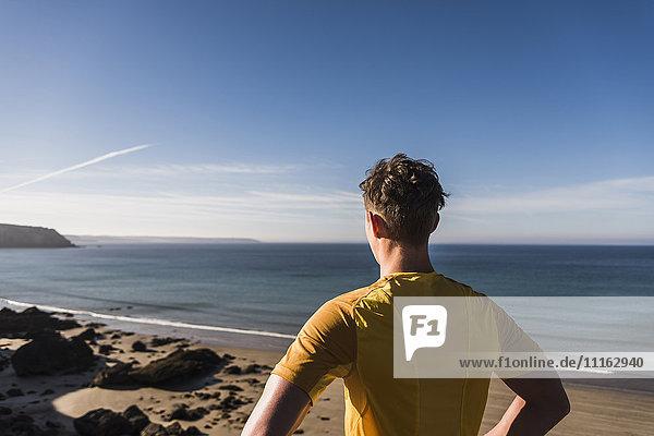 Frankreich,  Halbinsel Crozon,  sportlicher junger Mann an der Küste mit Blick auf die Küste