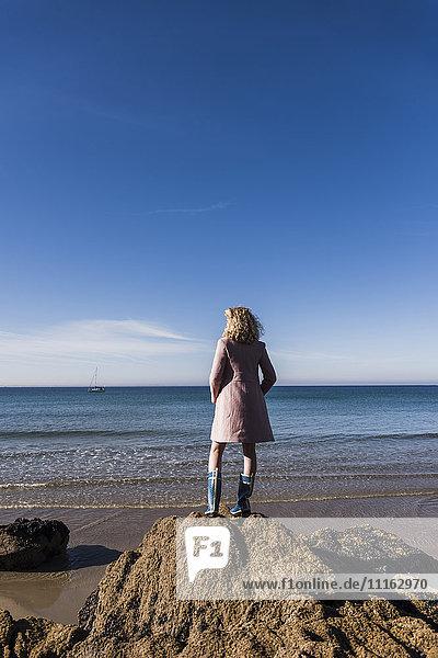 Frankreich  Halbinsel Crozon  Teenagermädchen auf Felsen am Strand stehend