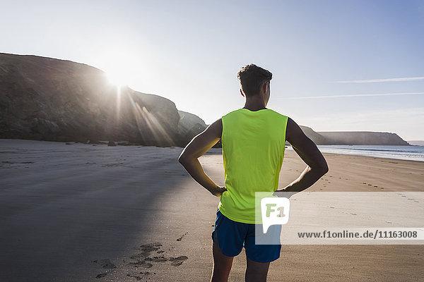 Frankreich  Halbinsel Crozon  sportlicher junger Mann am Strand stehend