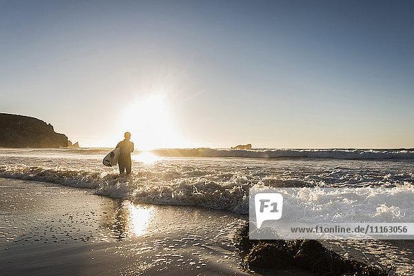 Frankreich  Bretagne  Halbinsel Crozon  Frau im Meer bei Sonnenuntergang mit Surfbrett
