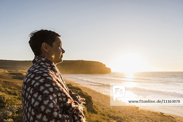 Frankreich  Bretagne  Halbinsel Crozon  Frau an der Küste bei Sonnenuntergang