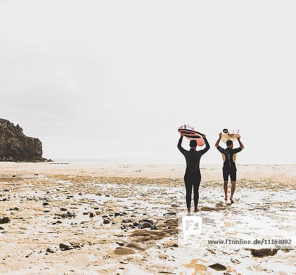 Frankreich  Bretagne  Halbinsel Crozon  Paar mit Surfbrettern am Strand spazieren gehen