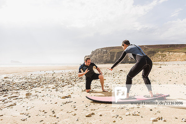 Frankreich  Bretagne  Halbinsel Crozon  Mann unterrichtet Frau beim Surfen am Strand