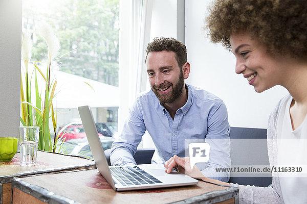 Junge Frau und Mann mit Laptop am Fenster