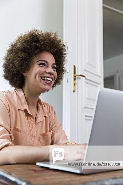 Lachende junge Frau mit Laptop